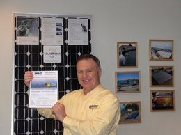 Owner, Buzz Burgett, showing the winning drawing for a free starter solar PV system